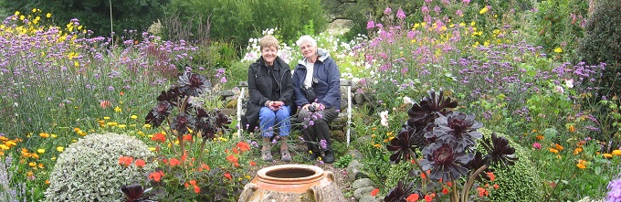 Mary Ann Thomas (left) and Jane Peloghitis enjoy a quiet moment in the gardens at Dyffryn Femant